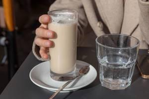 Eine Frau trinkt einen Latte Macchiatto in einem Cafe in Rom