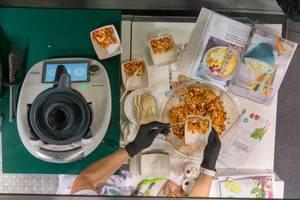 Eine Frau vorbereitet ein Gemüse-Gericht mit Hilfe des neuen Thermomix TM6 an der Fibo Fitnessmesse