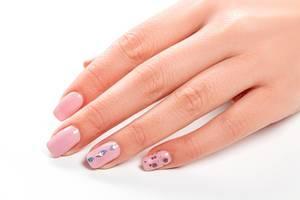 Eine Frauenhand mit rosa lackierten Fingernägeln auf weißem Hintergrund