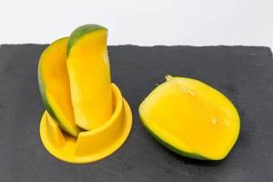 Eine frisch entsteinte Mango auf Schieferplatte