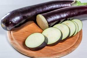 Eine Ganze und eine in Scheiben geschnittene Aubergine auf einem runden Holzbrett