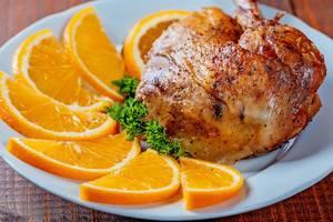 Eine Gebackene Entenkeule mit Orangen auf einem Teller in der Nahaufnahme