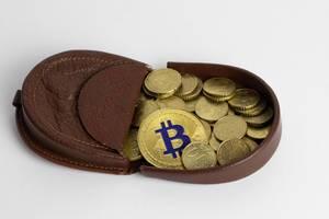 Eine Geldbörse mit Eurocent Münzen und einem Bitcoin