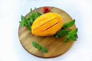 Eine geschnittene Mango mit Pfefferminzblättern auf einem runden Holzbrett