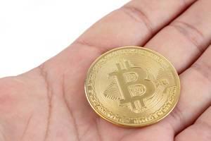Eine glänzend polierte Bitcoin-Münze liegt auf einer Hand