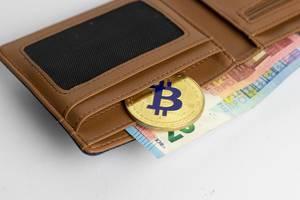 Eine goldene Bitcoinmünze in einer Geldbörse mit Euroscheinen