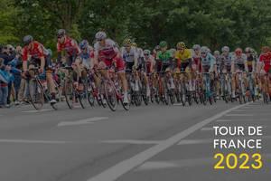 """Eine große Gruppe Radsportler beim Radrennen, neben der Aufschrift """"Tour de France 2023"""""""