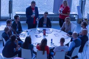 Eine Gruppe junger Unternehmer arbeiten an einem Projekt an rundem Tisch