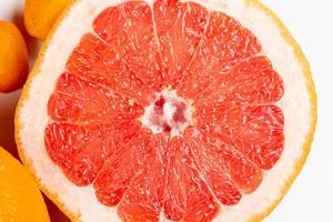 Eine halbe Grapefruit vor weißem Hintergrund in Nahaufnahme