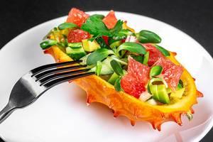 Eine halbe Kiwanofrucht gefüllt mit Avocado- und Grapefruitstückchen auf einem weißen Teller