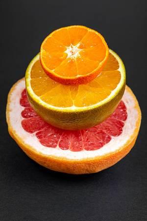 Eine halbe Orange, Grapefruit und ein halber Mandarin for schwarzem Hintergrund