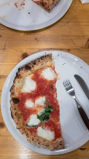 Eine Hälfte einer Margherita Pizza auf einem Teller mit Messer und Gabel im 485 Grad in Köln - Aufsicht