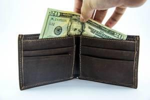 Eine Hand nimmt einen zwanzig Dollarschein aus einem dunkelbraunem Lederportmonnaie