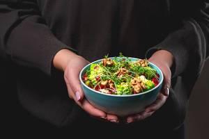 Eine in schwarz gekleidete Person hält einen Salat mit Walnusskernen, Mikrogrün, Romanesco Kohl und Granatapfelkernen in beiden Händen