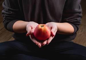 Eine in schwarz gekleidete Person im Schneidersitz hält einen frischen Apfel in beiden Händen