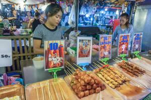 Eine junge Thailänderin verkauft verschiedene Fleischspezialitäten auf dem Mitternachtsmarkt in Bangkok