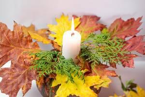 Eine Kerze leuchtet auf einem Kürbis mit Tannenzweigen und bunten Blättern