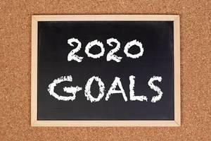 """Eine Kreidetafel zeigt den Text """"2020 Ziele"""" für das kommende Jahr, mit einer Korkplatte im Hintergrund"""