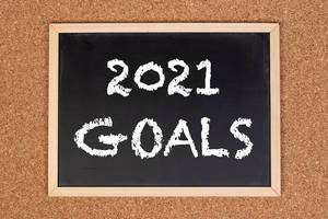 """Eine Kreidetafel zeigt den Text """"2021 Ziele"""" auf englisch, mit einer Korkwand im Hintergrund"""