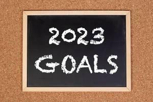 """Eine Kreidetafel zeigt den Text """"2023 Ziele"""" auf englisch, mit einer Pinnwand im Hintergrund"""