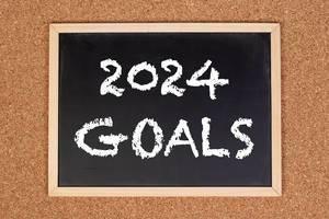 """Eine Kreidetafel zeigt den Text """"2024 Ziele"""" auf englisch, mit einer Korkwand im Hintergrund"""