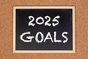 """Eine Kreidetafel zeigt den Text """"2025 Goals"""" - zu deutsch: 2025 Ziele , mit einer Korkwand im Hintergrund"""