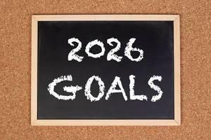 """Eine Kreidetafel zeigt den Text """"2026 Ziele"""" auf englisch, mit einer Korkwand im Hintergrund"""