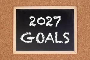 """Eine Kreidetafel zeigt den Text """"2027 Ziele"""" auf englisch, mit einer Korkwand im Hintergrund"""