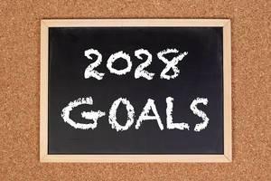 """Eine Kreidetafel zeigt den Text """"2028 Ziele"""" auf englisch, mit einer Korkwand im Hintergrund"""