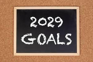 """Eine Kreidetafel zeigt den Text """"2029 Ziele"""" auf englisch, mit einer Korkwand im Hintergrund"""