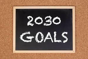 """Eine Kreidetafel zeigt den Text """"2030 Ziele"""" auf englisch, mit einer Korkwand im Hintergrund"""