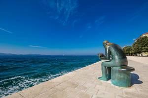 Eine Kupferstatue eines Mannes mit einer Muschel in den Händen an einer Promenade