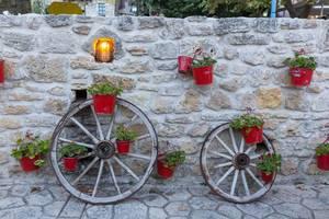 Eine Mauer mit roten Blumeneimern in Afitos