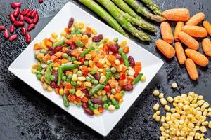 Eine Mischung aus fein geschnittenem buntem Gemüse auf einem Teller auf einem schwarzen Hintergrund