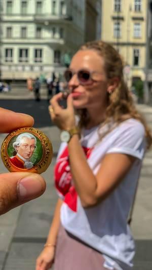 Eine Mozartkugel zwischen den Fingern, junge Frau im unscharfen Hintergrund