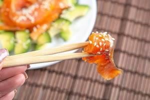 Eine Person hält ein Stück Räucherlachs mit Sesam über einem Teller mit Avocado-Lachs Salat auf einer Bambusmatte Nahaufnahme