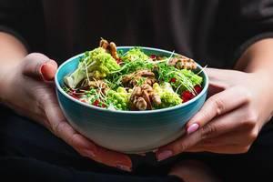 Eine Person hält eine Keramik Schale mit Salat mit Walnusskernen, Mikrogrün und Romanesco Kohl Nahaufnahme