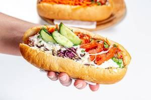 Eine Person hält einen Hot Dog mit Kohl, Gurken, Tomaten, Karotten und Saucen