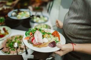 Eine Person hält einen Teller mit Schweinefleisch und gemischtem Gemüse vor einem Buffet