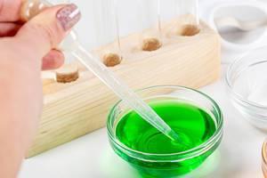 Eine Person hält Pipette in eine Schale mit grüner Flüssigkeit um einen Labortest durchzuführen