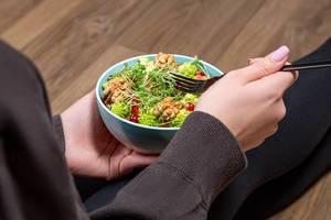 Eine Person isst einen Fitness Salat mit Walnusskernen, Mikrogrün, Romanesco Kohl und Granatapfelkernen mit einer Gabel Nahaufnahme
