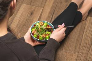 Eine Person isst einen Salat mit Walnusskernen, Mikrogrün, Romanesco Kohl und Granatapfelkernen mit einer Gabel