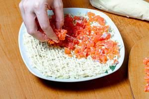Eine Person legt geschnittenen Lachs auf einen Teller mit Salat