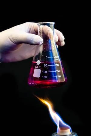 Eine Person mit Gummihandschuh hält ein Erlenmeyerkolben mit Flüssigkeit über eine Flamme mit schwarzem Hintergrund