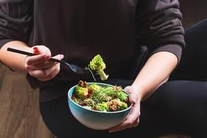 Eine Person mit schwarzer Kleidung isst einen gesunden Salat mit Romanesco Kohl, Mikrogrün und Walnusskernen