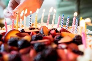 Eine Person zündet Kerzen auf einem Obstkuchen an