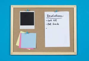 Eine Pinnwand mit einer Liste mit Vorsätzen für das Jahr 2019, einem leeren Polaroid Sofortbild und Stickynotes