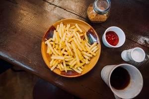 Eine Portion Pommes mit Kaffee in einem Restaurant - Aufsicht