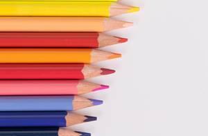 Eine Reihe Buntstifte vor weißem Hintergrund: blau, lila, rot, gelb
