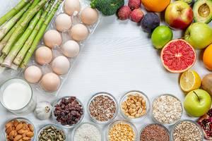 Eine Reihe von Lebensmitteln, die für das Gehirn nützlich sind, auf einem weißen, hölzernen Hintergrund mit freiem Platz